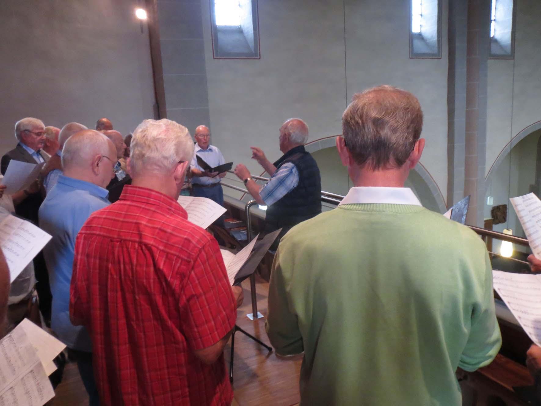 Chor mit Dirigent vor Orgel